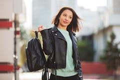 Mulher nova da forma no casaco de cabedal preto que anda na rua da cidade Fotografia de Stock