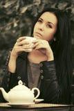 Mulher nova da forma no chá bebendo do casaco de cabedal no passeio cae imagem de stock royalty free