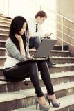 Mulher nova da forma que usa o portátil nas etapas Foto de Stock