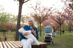 Mulher nova da mãe que aprecia o tempo livre com sua criança do bebê - criança branca caucasiano com a mão de um pai visível - foto de stock royalty free