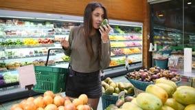 Mulher nova da raça misturada que escolhe abacates na mercearia Da menina zero do desperdício do vegetariano frutos de compra e v filme