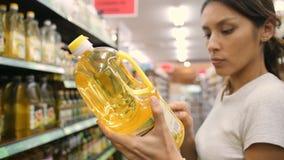 Mulher nova da raça misturada que escolhe o azeite no supermercado Os ingredientes da leitura do cliente etiquetam na loja 4K filme