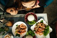 Mulher nova de Ásia da vista superior que come no restaurante com frie do marisco Imagens de Stock
