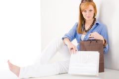 Mulher nova de compra com assento do saco de papel Fotografia de Stock Royalty Free