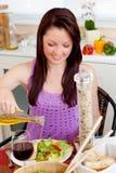 Mulher nova de incandescência que come uma salada com petróleo imagens de stock