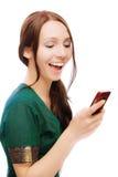 A mulher nova de riso lê sms Fotos de Stock