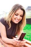 A mulher nova de riso lê sms Fotografia de Stock Royalty Free