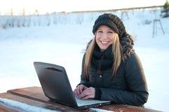 Mulher nova de sorriso com o portátil no inverno Fotos de Stock Royalty Free