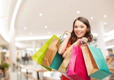 Mulher nova de sorriso com sacos de compra Foto de Stock Royalty Free