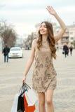 Mulher nova de sorriso com sacos de compra Foto de Stock