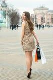 Mulher nova de sorriso com sacos de compra Fotografia de Stock Royalty Free