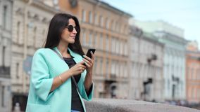 Mulher nova de sorriso do curso da forma que toma a foto usando o smartphone que admira a arquitetura histórica filme