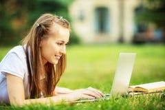A mulher nova de sorriso do estudante está usando um portátil e está liying no Foto de Stock Royalty Free