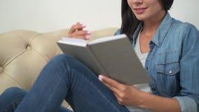 Mulher nova de sorriso que lê um livro vídeos de arquivo