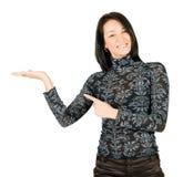 Mulher nova de sorriso que mostra algo em sua mão Fotografia de Stock Royalty Free