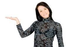 Mulher nova de sorriso que mostra algo em sua mão Imagem de Stock