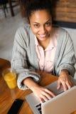Mulher nova de sorriso que usa o portátil em casa Fotografia de Stock Royalty Free