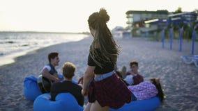 A mulher nova despreocupada do moderno com teme dançar no por do sol com grupo de amigos que sentam-se em easychairs na praia filme