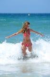 Mulher nova do ajuste 'sexy' que está sendo espirrada por uma onda Foto de Stock Royalty Free