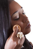 Mulher nova do americano africano que aplica a face da composição Fotos de Stock