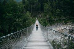 A mulher nova do caminhante anda na ponte de suspensão imagem de stock royalty free