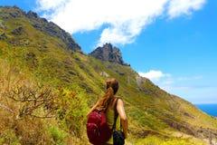 Mulher nova do caminhante que olha o pico da montanha que pensa que é muito necessário obter à parte superior foto de stock