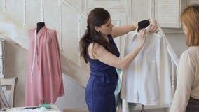 A mulher nova do desenhista do clother mostra o resultado final a seu cliente no estúdio do alfaiate