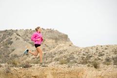 Mulher nova do esporte que foge a estrada suja da fuga da estrada com o fundo seco da paisagem do deserto que treina duramente imagem de stock royalty free