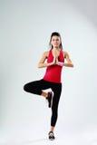 Mulher nova do esporte que medita ao estar em um pé Fotos de Stock Royalty Free