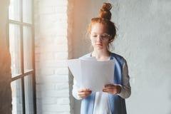 Mulher nova do estudante do moderno ou desenhista autônomo criativo que trabalham no projeto Guardando o coursework ou o plano de imagem de stock