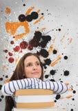 Mulher nova do estudante que olha acima contra o fundo chapinhado cinzento, amarelo e preto Fotos de Stock Royalty Free