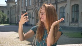 Mulher nova do gengibre que toma o selfie e que verifica seu telefone, problema com dispositivo, estando na rua e sorrindo, const filme