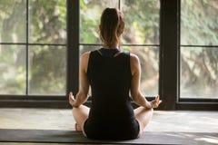 Mulher nova do iogue na pose de Sukhasana, fundo da janela foto de stock