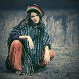 Mulher nova do moderno da forma no poncho do rasta que senta-se na terra Fotos de Stock