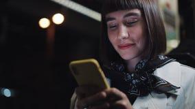 A mulher nova do moderno que usa o smartphone que senta em público o transporte, steadicam disparou Est? sorrindo Movimento lento filme