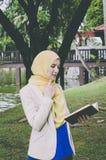 Mulher nova do muslimah da cara do sorriso que está e que guarda cadernos no parque Imagem de Stock