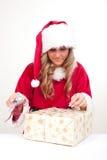 A mulher nova do Natal está abrindo presentes de um xmas Imagem de Stock