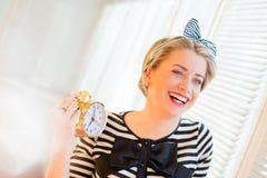 Mulher nova do pinup que mostra o alarme e o riso Fotografia de Stock Royalty Free