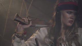 A mulher nova do pirata com uma pistola está olhando em torno do navio, 4k video estoque