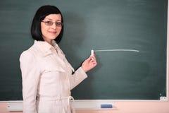 Mulher nova do professor na placa verde imagens de stock