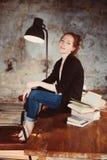 Mulher nova do ruivo do moderno que relaxa em casa, sentando-se na tabela de madeira com livros fotografia de stock royalty free
