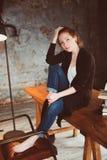 Mulher nova do ruivo do moderno que relaxa em casa, sentando-se na tabela de madeira com livros fotos de stock
