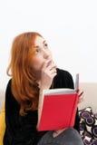 Mulher nova do ruivo pensativa com um livro imagens de stock royalty free
