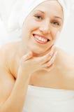 Mulher nova do smiley com creme de face após o chuveiro fotografia de stock