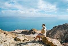 A mulher nova do turista está sentando-se na parte superior da montagem e está olhando-se uma paisagem bonita da baía do mar fotos de stock