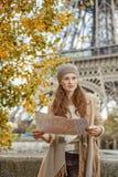 Mulher nova do turista na terraplenagem em Paris, França com mapa Fotografia de Stock Royalty Free