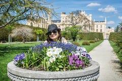 A mulher nova do turista que levantam com canteiro de flores e Lednice fortificam dentro Imagem de Stock