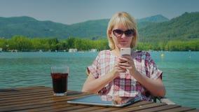 Mulher nova do turista que relaxa em um lugar bonito pelo lago e pelas montanhas Usa o telefone, sentando-se em uma tabela dentro video estoque