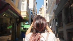 Mulher nova do turista que toma imagens de ruas de Istambul usando o telefone celular Turquia 4K Slowmotion vídeos de arquivo