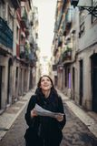 Mulher nova do viajante que admira ruas estreitas ensolaradas bonitas em Lisboa, Portugal imagens de stock royalty free